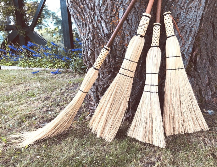 photo of four handmade brooms propped up against a tree trunk with autumn foliage in the background