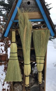 photo of 3 handmade brooms in front of a weathered birdhouse, with snow on the ground